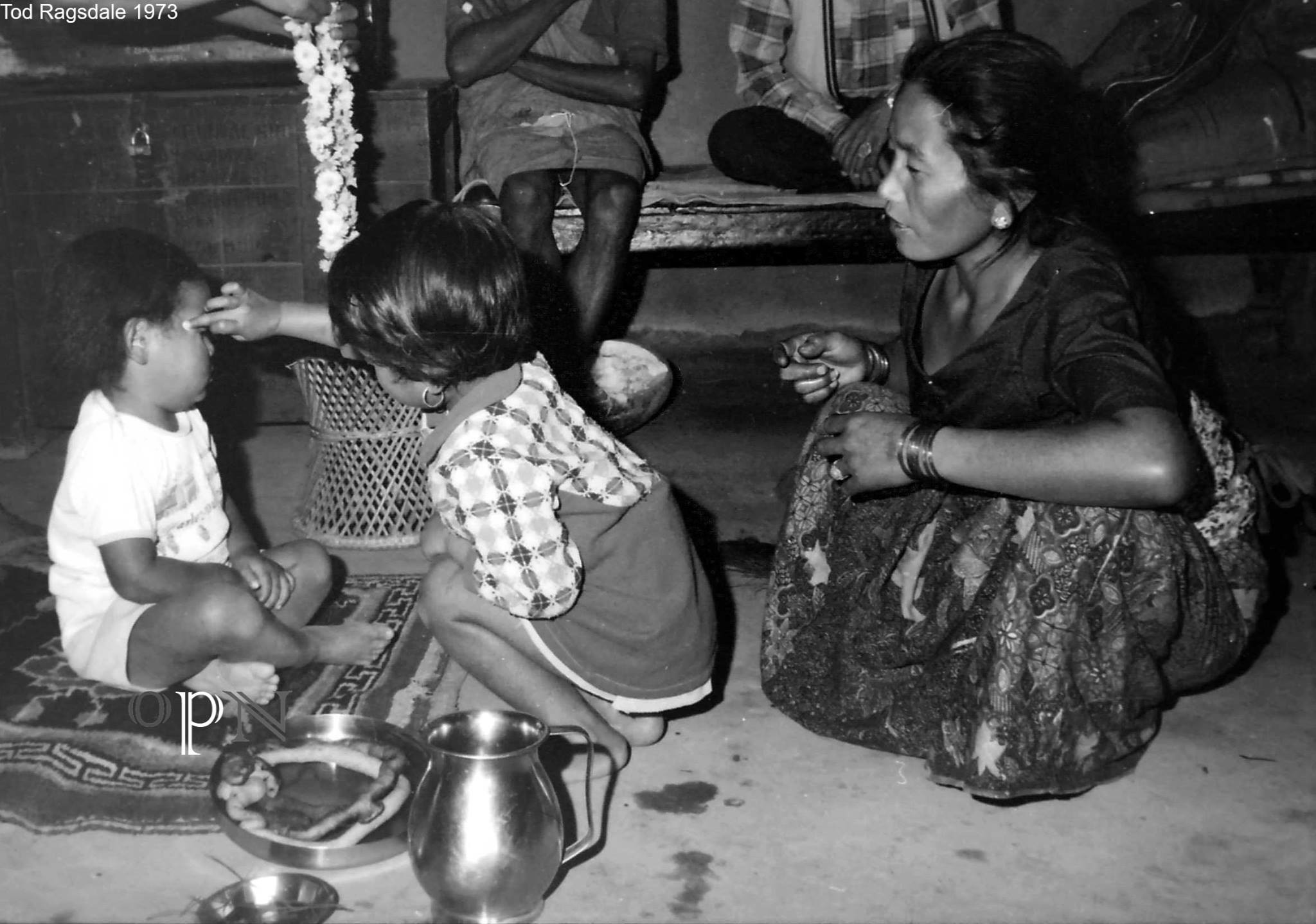 A little girl applying bhai tika to her brother in Mauja, Kaski in 1973. old nepal